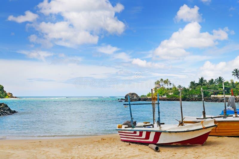 Barco de pesca na costa e no oceano arenosos imagem de stock