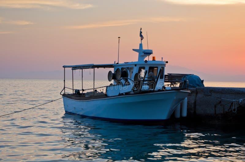 Barco de pesca na doca no por do sol imagem de stock