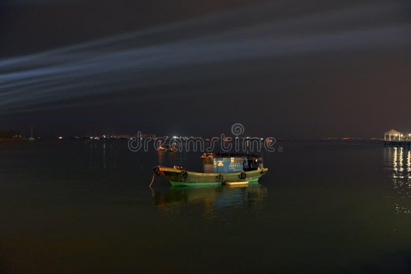 Barco de pesca na noite no projetor fotografia de stock
