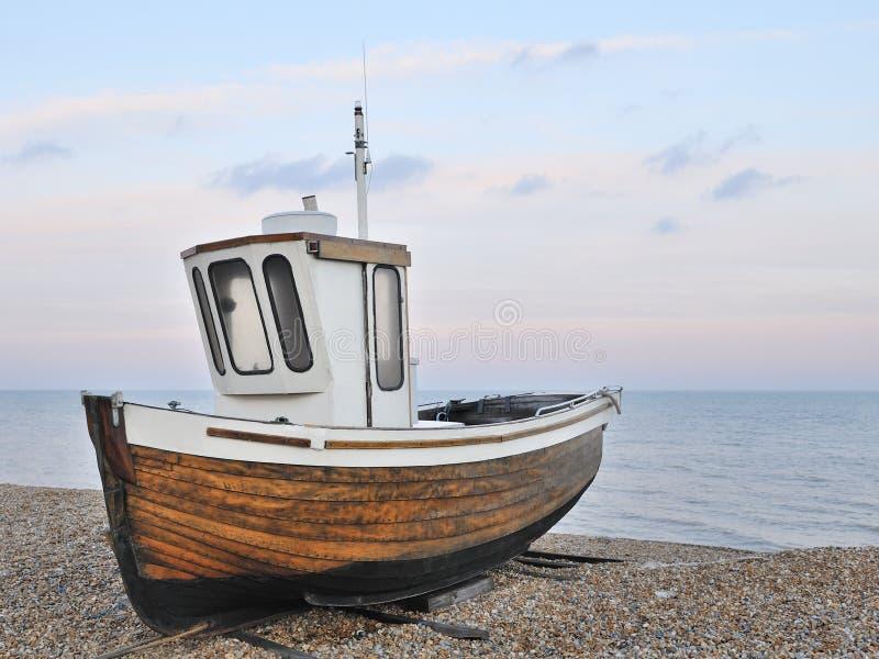 Barco de pesca na praia do cascalho fotos de stock royalty free