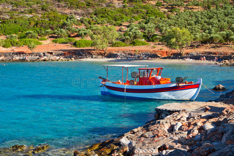 Barco de pesca na praia idílico em Crete imagem de stock