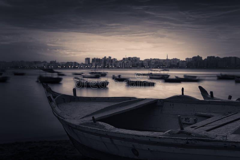 Barco de pesca na praia no nascer do sol com skyline de Alexandria na distância distante no nascer do sol foto de stock royalty free