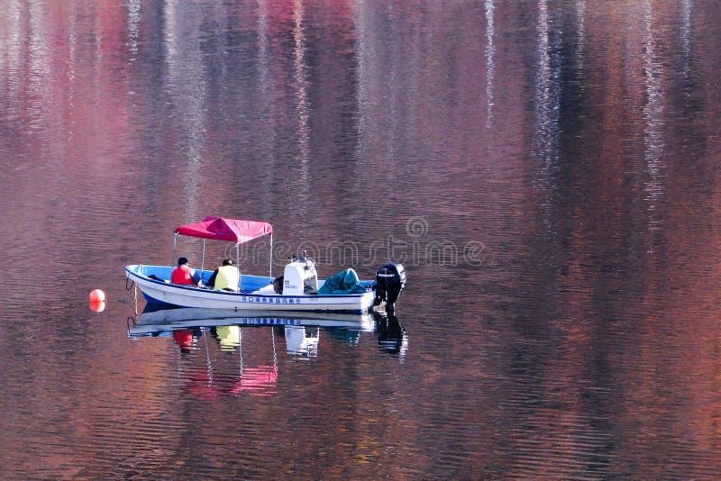 Barco de pesca no lago do outono imagem de stock