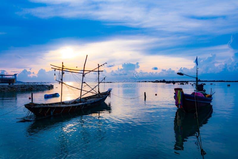 Barco de pesca no mar, no por do sol e nas silhuetas de barcos de madeira foto de stock royalty free