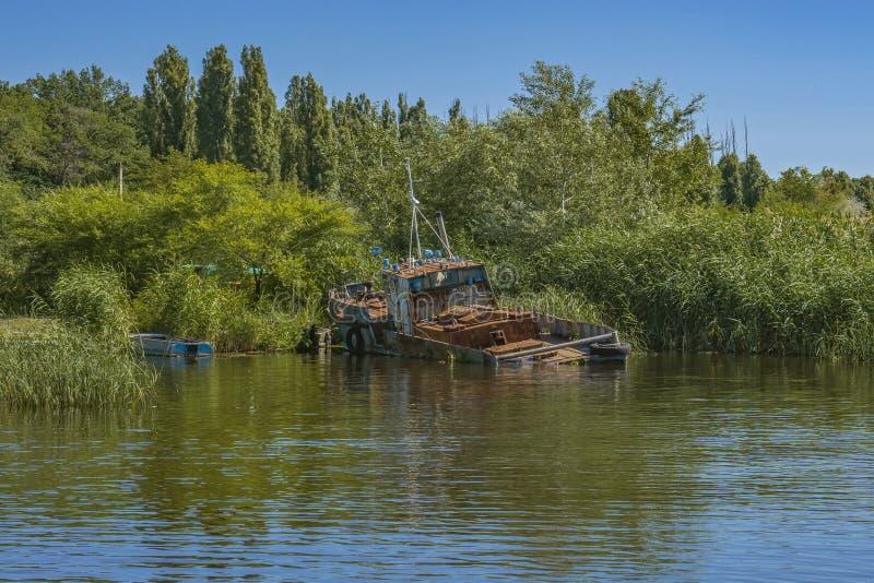 Barco de pesca oxidado viejo abandonado en orilla foto de archivo libre de regalías