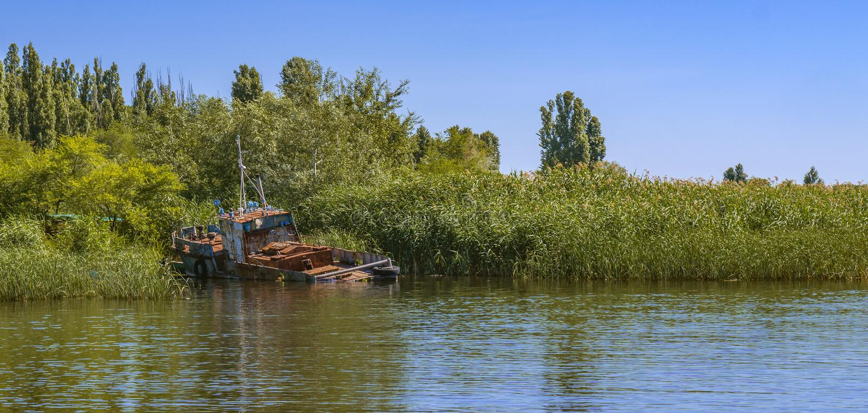 Barco de pesca oxidado viejo abandonado en orilla foto de archivo