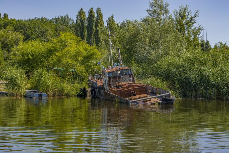 Barco de pesca oxidado viejo abandonado en orilla imagenes de archivo