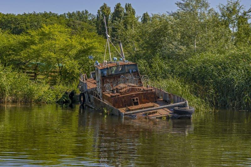 Barco de pesca oxidado viejo abandonado en orilla imagen de archivo libre de regalías