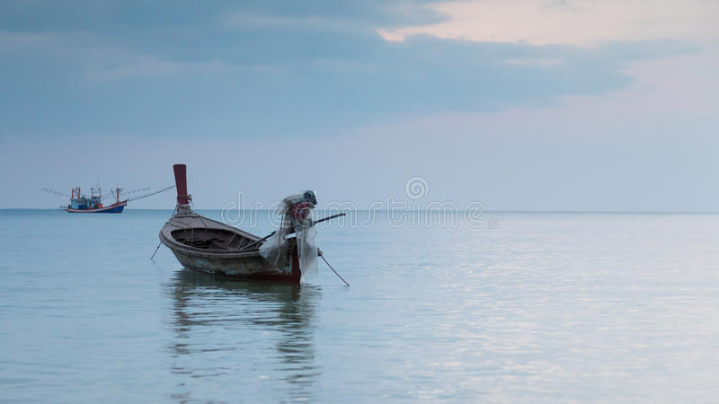 Barco de pesca pequeno no mar durante o céu crepuscular fotos de stock