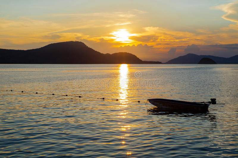 Barco de pesca pequeno no mar, tempo crepuscular com sóis bonitos imagens de stock