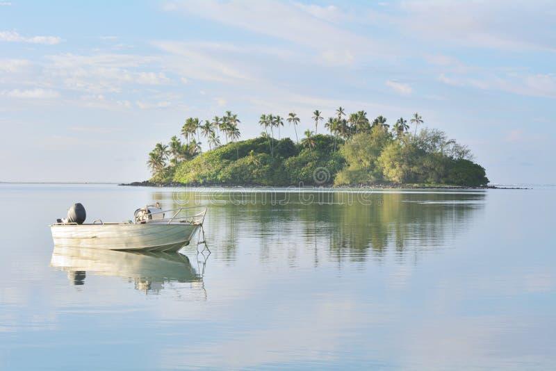 Barco de pesca que amarra sobre las aguas tranquilas en la laguna Rarotonga C de Muri fotos de archivo