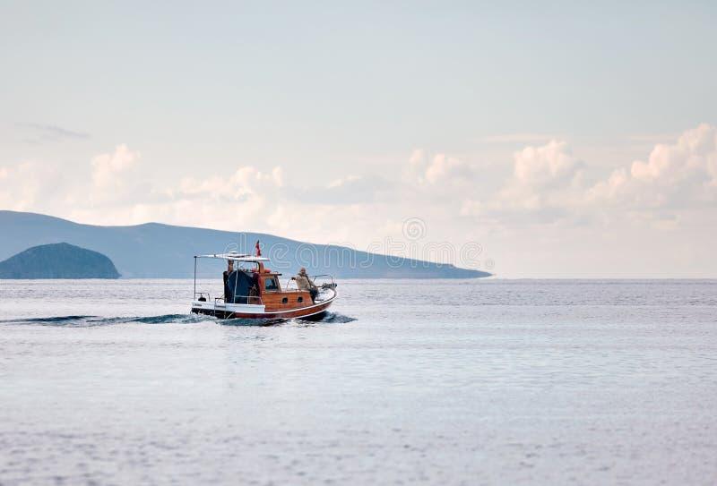 Barco de pesca que leva uma navigação de dois pescadores sobre o mar calmo no tempo de inverno em Gumusluk, Bodrum, Turquia fotos de stock royalty free