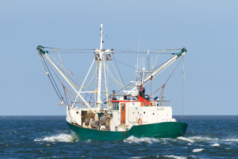 Barco de pesca que navega hacia fuera en el océano la captura algunos pescados en el Mar del Norte imagenes de archivo