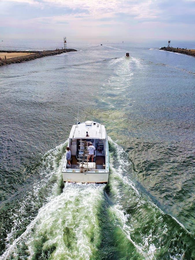 Barco de pesca que navega para fora de no meio dois cais em sua maneira a t foto de stock