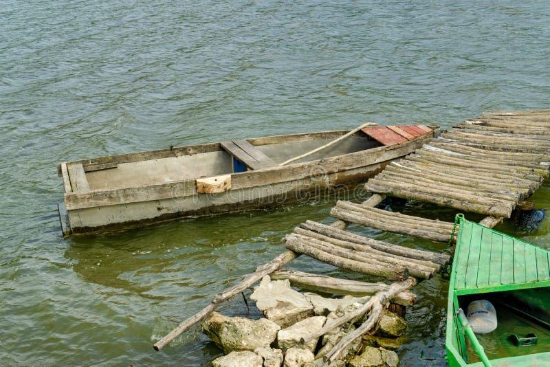 Barco de pesca que rema de madera viejo amarrado cerca del lago imagen de archivo libre de regalías