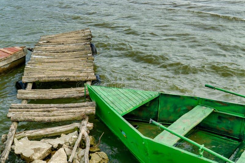 Barco de pesca que rema de madera viejo amarrado cerca del lago imagenes de archivo