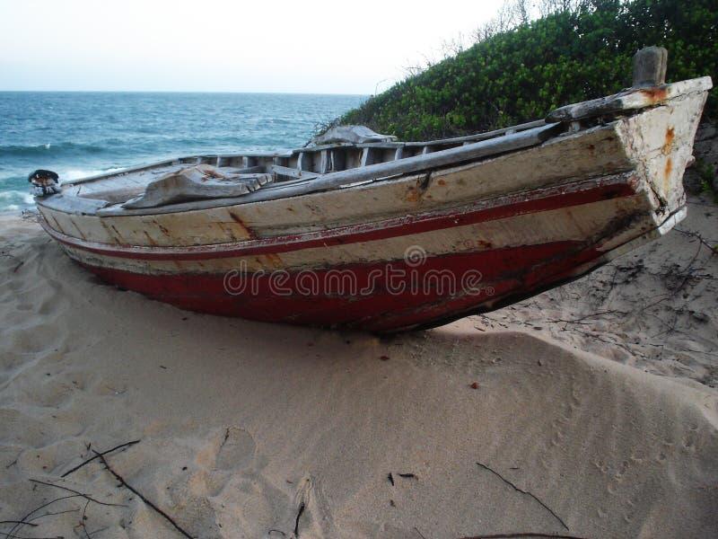 Barco de pesca rojo trenzado en la playa fotografía de archivo