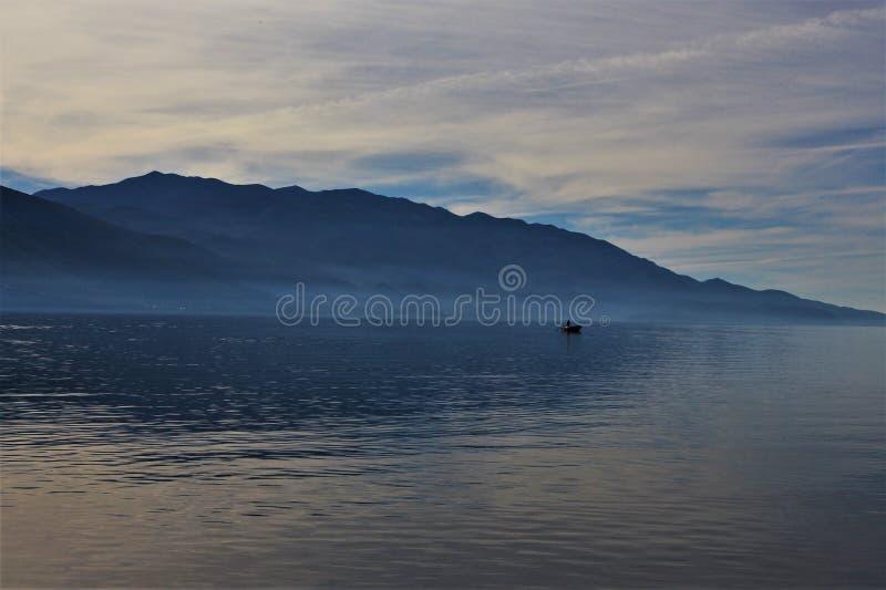 Barco de pesca só na água azul imagens de stock royalty free