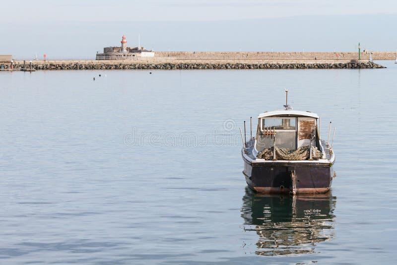 Barco de pesca solitario anclado en el puerto de piedra imagen de archivo libre de regalías