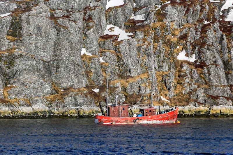 Barco de pesca solitario que flota cerca del acantilado escarpado, fiordo de Nuuk, Greenla fotografía de archivo libre de regalías