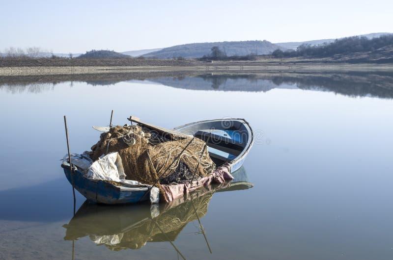 Barco de pesca solo en el lago con la reflexión fotos de archivo