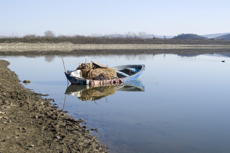 Barco de pesca solo en el lago con la reflexión fotos de archivo libres de regalías