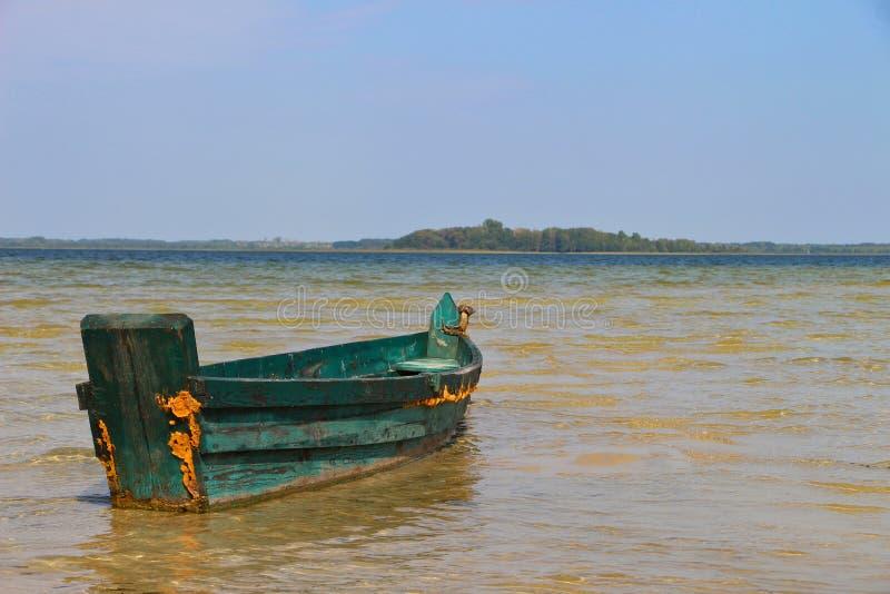 Barco de pesca verde de madera del viejo vintage en el agua clara con horizonte fotos de archivo libres de regalías