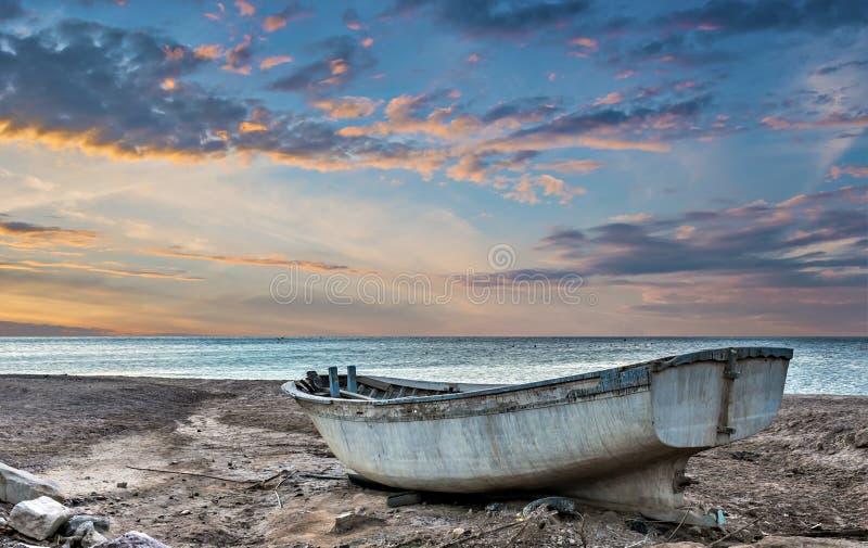 Barco de pesca viejo en la puesta del sol imagenes de archivo