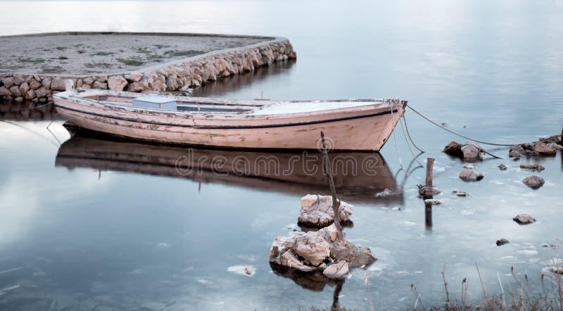 Barco de pesca viejo tradicional en el puerto, agua sedosa, exposición larga imagen de archivo