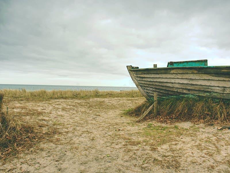 Barco de pesca Wrecked en hierba seca vieja Nave de madera abandonada con el motor dañado imagenes de archivo