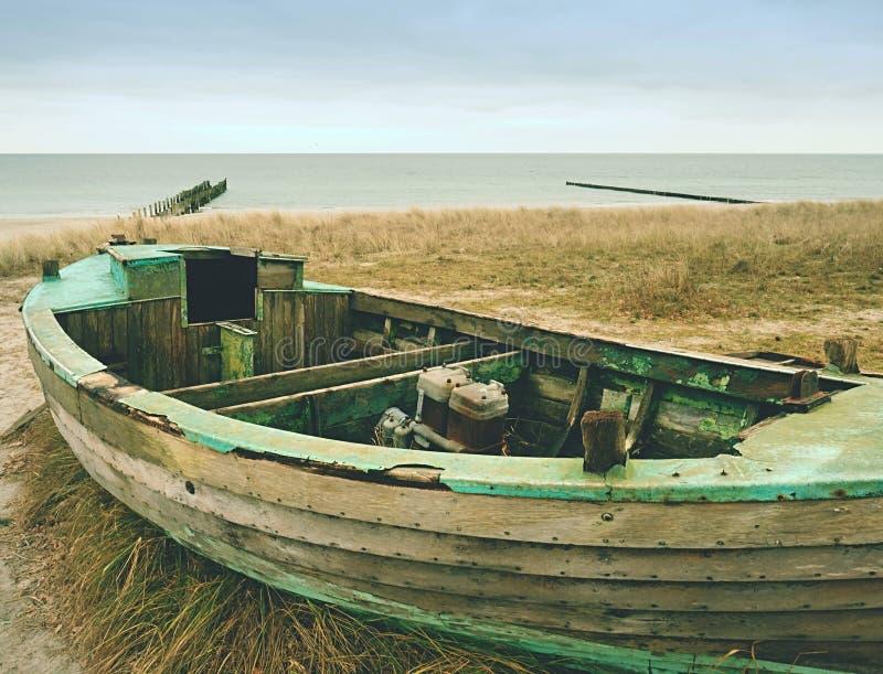 Barco de pesca Wrecked en hierba seca vieja Nave de madera abandonada con el motor dañado imagen de archivo libre de regalías