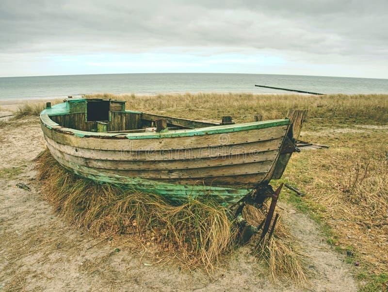 Barco de pesca Wrecked en hierba seca vieja Nave de madera abandonada con el motor dañado fotos de archivo