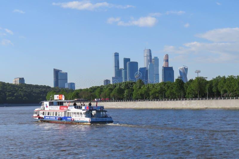 Barco de placer con los pasajeros que navegan en el río de Moscú En el fondo son los rascacielos de la ciudad de Moscú internacio fotos de archivo libres de regalías