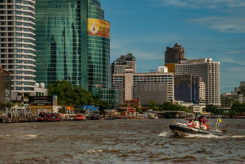 Barco de policía que acomete en superficie del agua contra de Chao Phraya Riverembankment With el contexto de un edificio moderno fotografía de archivo