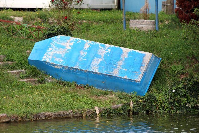 Barco de río azul viejo con el color dilapidado sacado del agua para la restauración rodeada con la hierba y las flores sin corta fotos de archivo