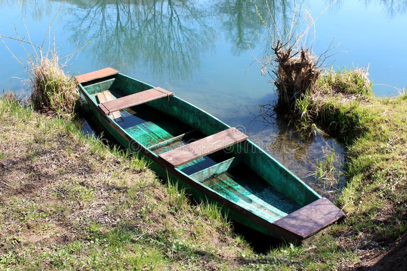 Barco de río dilapidado con la pintura descolorada asegurada en la orilla del río local rodeada con agua de río tranquila y la hi fotos de archivo