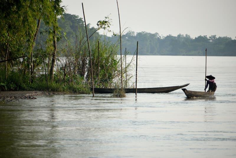 Barco de río en el agua que se desliza a través con el barquero, con otro ocultado detrás de bambúes imagen de archivo