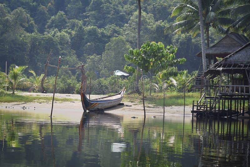 Barco de río largo camboyano tradicional levantado en la playa por una casa de madera en la selva foto de archivo libre de regalías