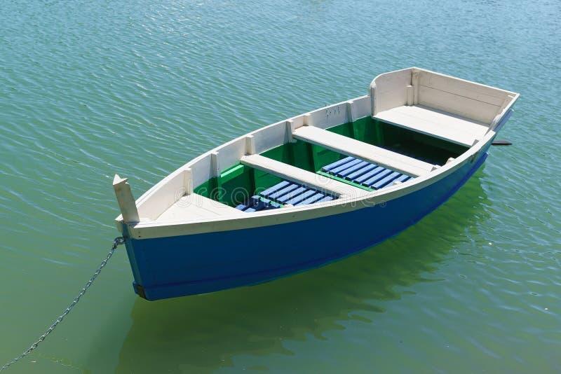 Barco de rowing azul brillante en el agua esmeralda del lago fotos de archivo libres de regalías