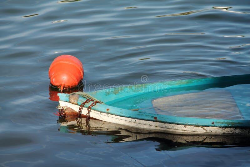 Barco de rowing azul viejo abandonado que se ahoga en puerto fotos de archivo libres de regalías