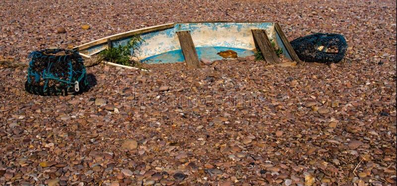 Barco de rowing enterrado en la playa de Sidmouth fotografía de archivo libre de regalías