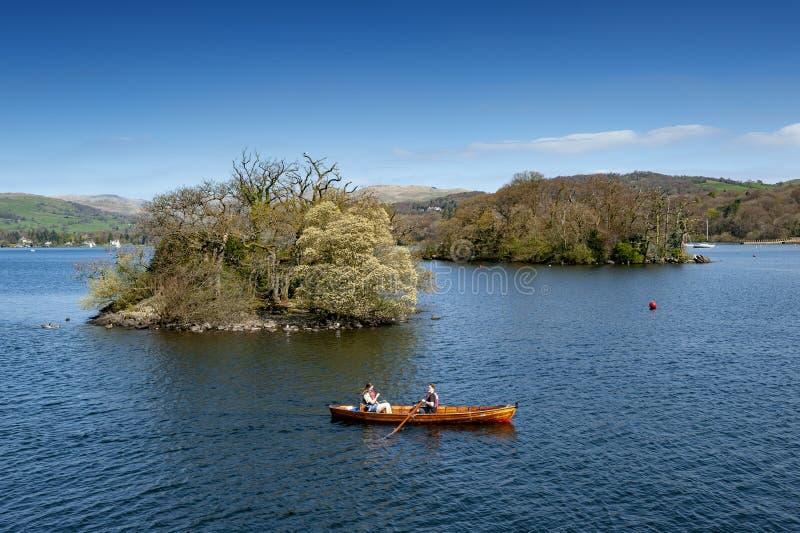 Barco de rowing de los turistas en el lago escénico Windermere en el parque nacional del distrito del lago, Inglaterra del noroes fotografía de archivo