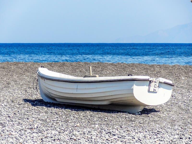 Barco de rowing solo en la playa pebbled de Santorini Grecia fotografía de archivo