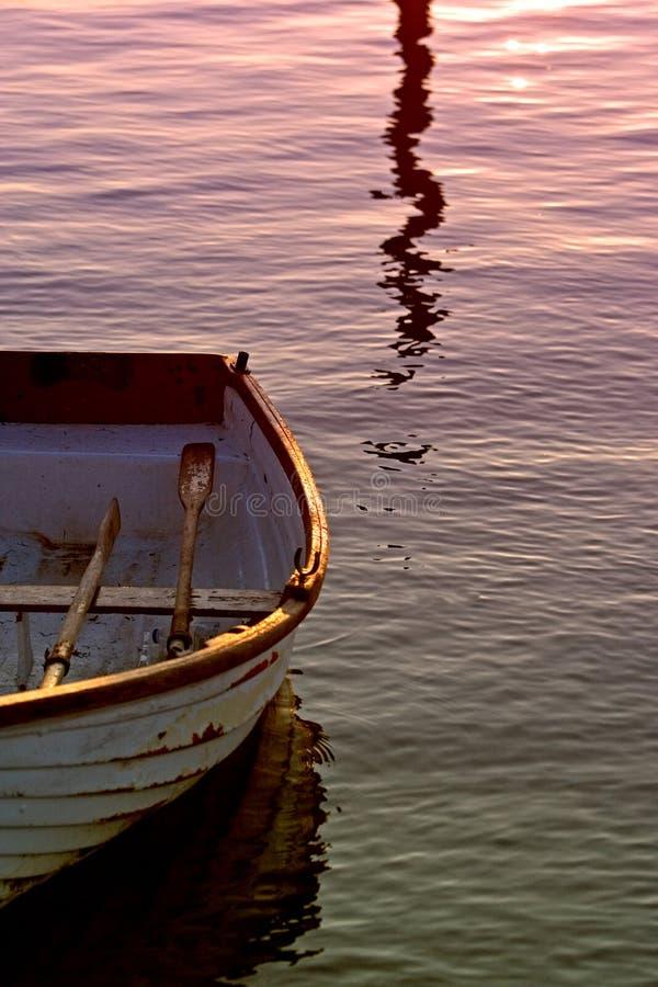 Barco de Rowing viejo con los remos en el mar durante puesta del sol fotos de archivo