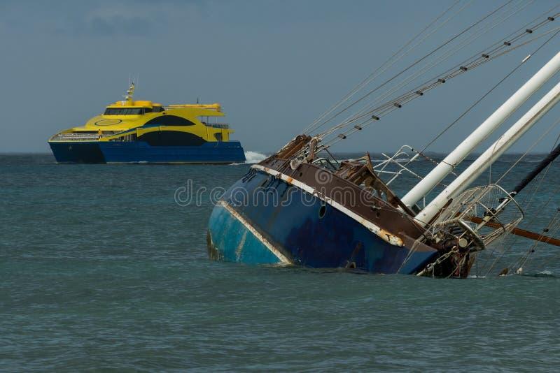 Barco de vela afundado na frente de uma balsa amarela brilhante do passanger no clima de tempestade nas Caraíbas ocidentais fotos de stock royalty free
