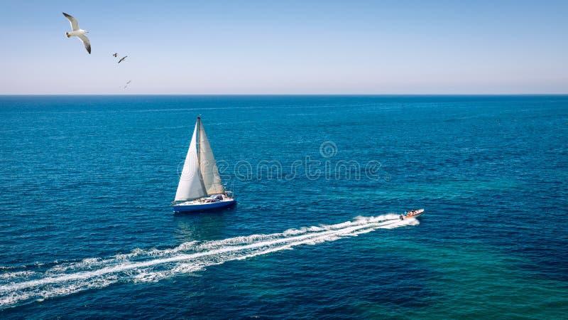 Barco de vela blanco aislado en agua de mar azul Velero en el mar en la luz del sol, aventura de lujo del verano, vacaciones acti imagen de archivo