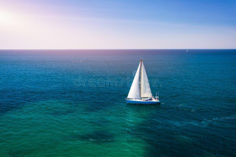 Barco de vela blanco aislado en agua de mar azul Velero en el mar en la luz del sol, aventura de lujo del verano, vacaciones acti foto de archivo libre de regalías