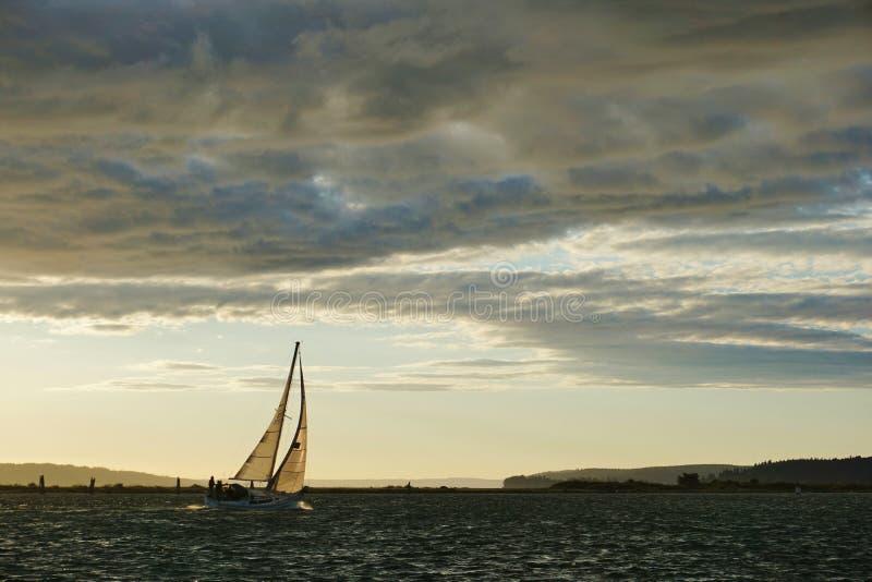 Barco de vela con la vela llena en la puesta del sol en Puget Sound fotos de archivo libres de regalías