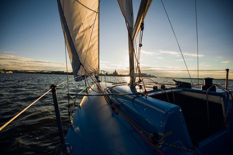 Barco de vela con las velas puestas que se deslizan en un mar o un río en la puesta del sol fotos de archivo libres de regalías