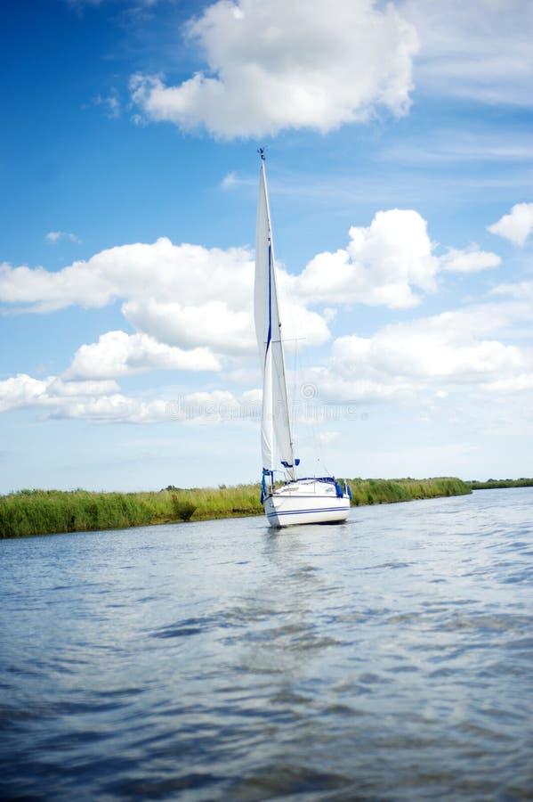 Barco de vela de Norfolk Broads que navega abaixo de um rio imagem de stock royalty free